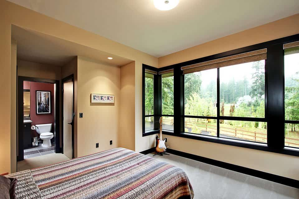 Another bedroom with its own bathroom. It showcases a cozy bed covered in a striped blanket.