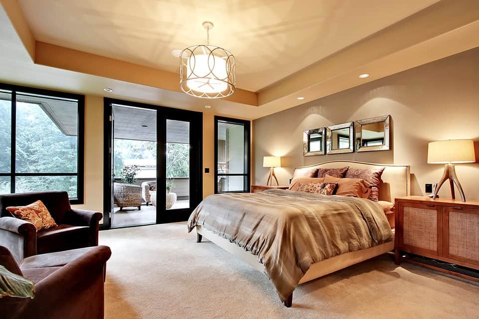 The primary bedroom showcases a stunning tray ceiling and a french door leading out to its own covered porch.