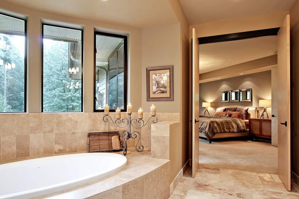 The primary bathroom is enclosed in a wooden double door. It has a deep soaking tub placed under the bay window.