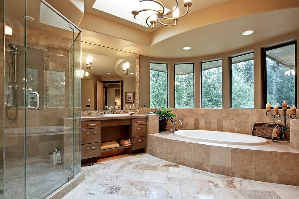 This primary bathroom exudes opulence with its corner shower, a sink vanity, and a deep soaking tub topped with panoramic windows. The bright natural light from the windows and skylight is balanced by the warm glow of sconces and chandeliers.