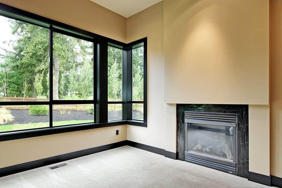 The huge bonus room has a modern fireplace and black framed windows overlooking the garden.