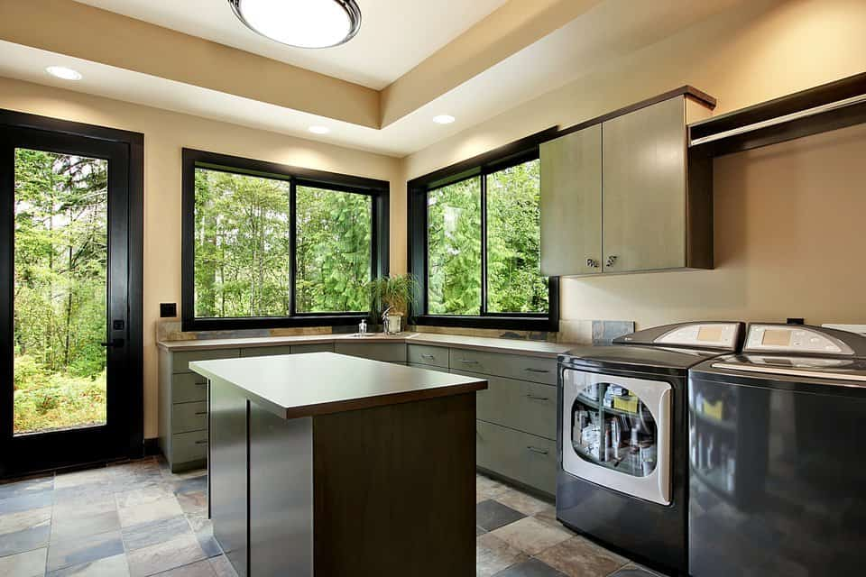 The utility room is equipped with washing machine and dryer. There are also cabinets and an island sitting under the glass flush light.