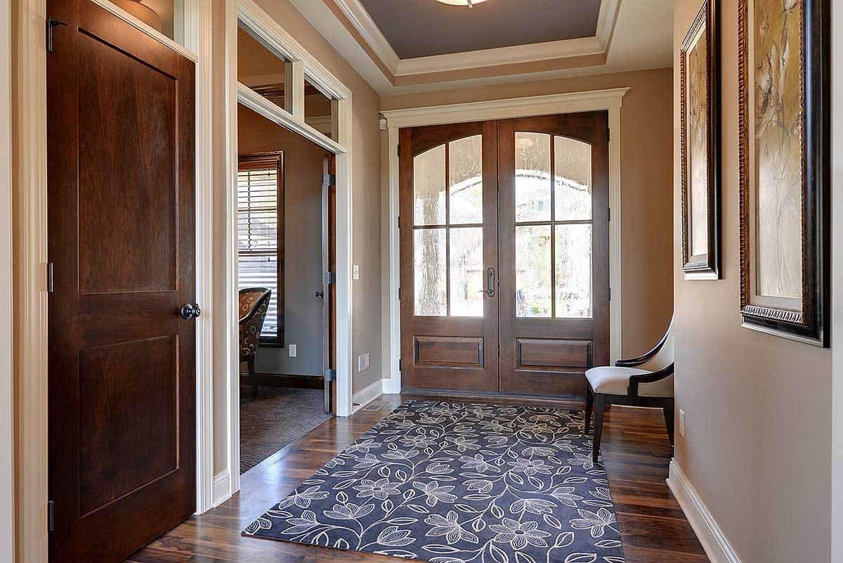 The foyer with a gray tray ceiling and rich hardwood flooring topped by a large floral rug. It includes a beige cushioned chair facing the home office.
