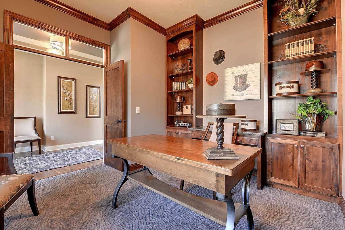 A wooden double door opens to the home office with built-in shelving and a wooden desk paired with a cushioned chair.