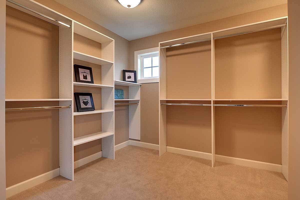 Spacious walk-in closet filled with built-in shelving and chrome hanger rods. It is illuminated by a warm glass dome flush light.