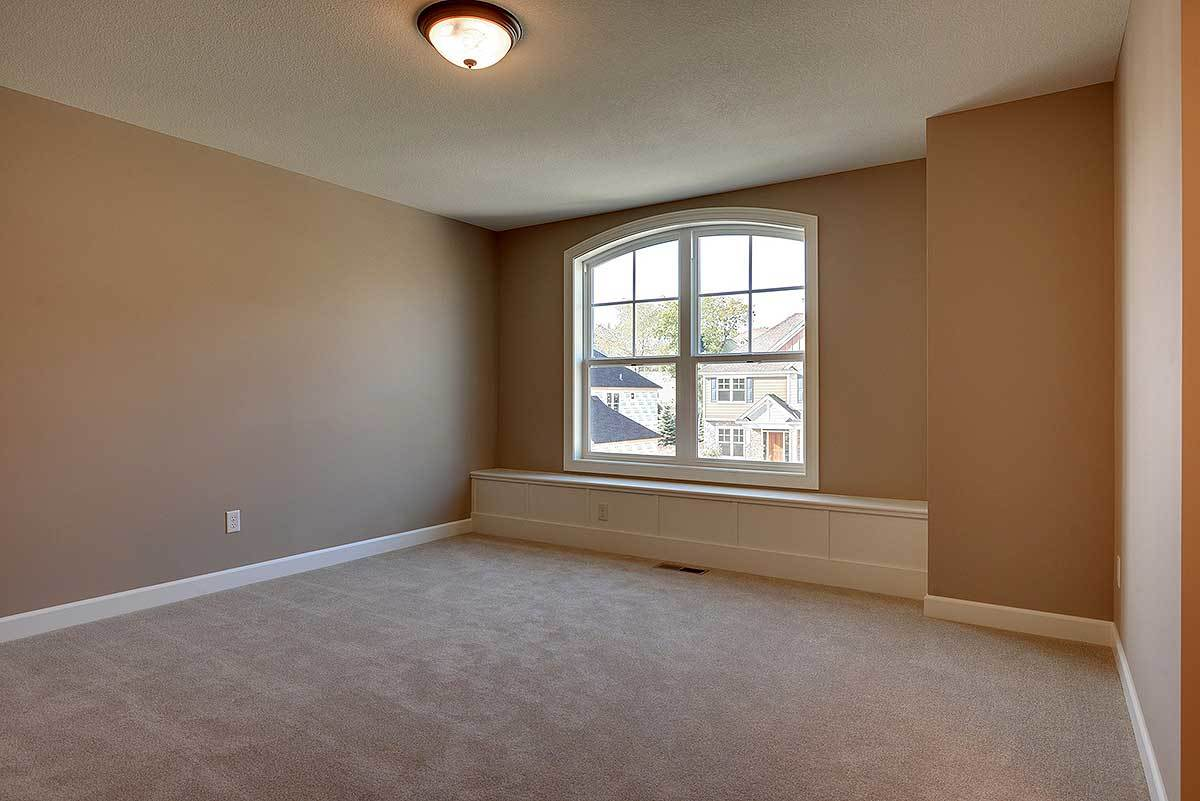 An empty bedroom with carpet flooring and dark beige walls contrasted by white base molding. There's a built-in seat nook under the arched window.