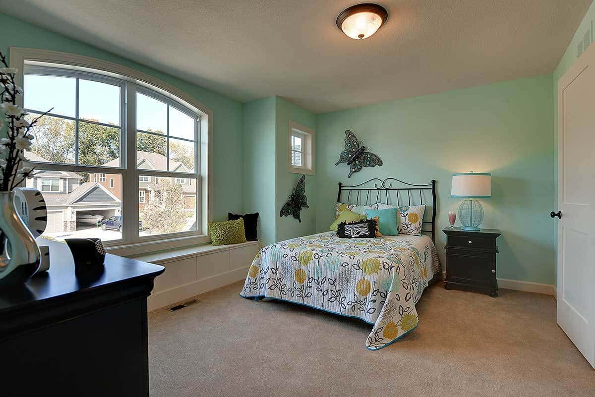 The kid's bedroom boasts a metal bed and a dark wood nightstand topped by a cute drum lamp. It has a window seat and green walls adorned by lovely butterflies.