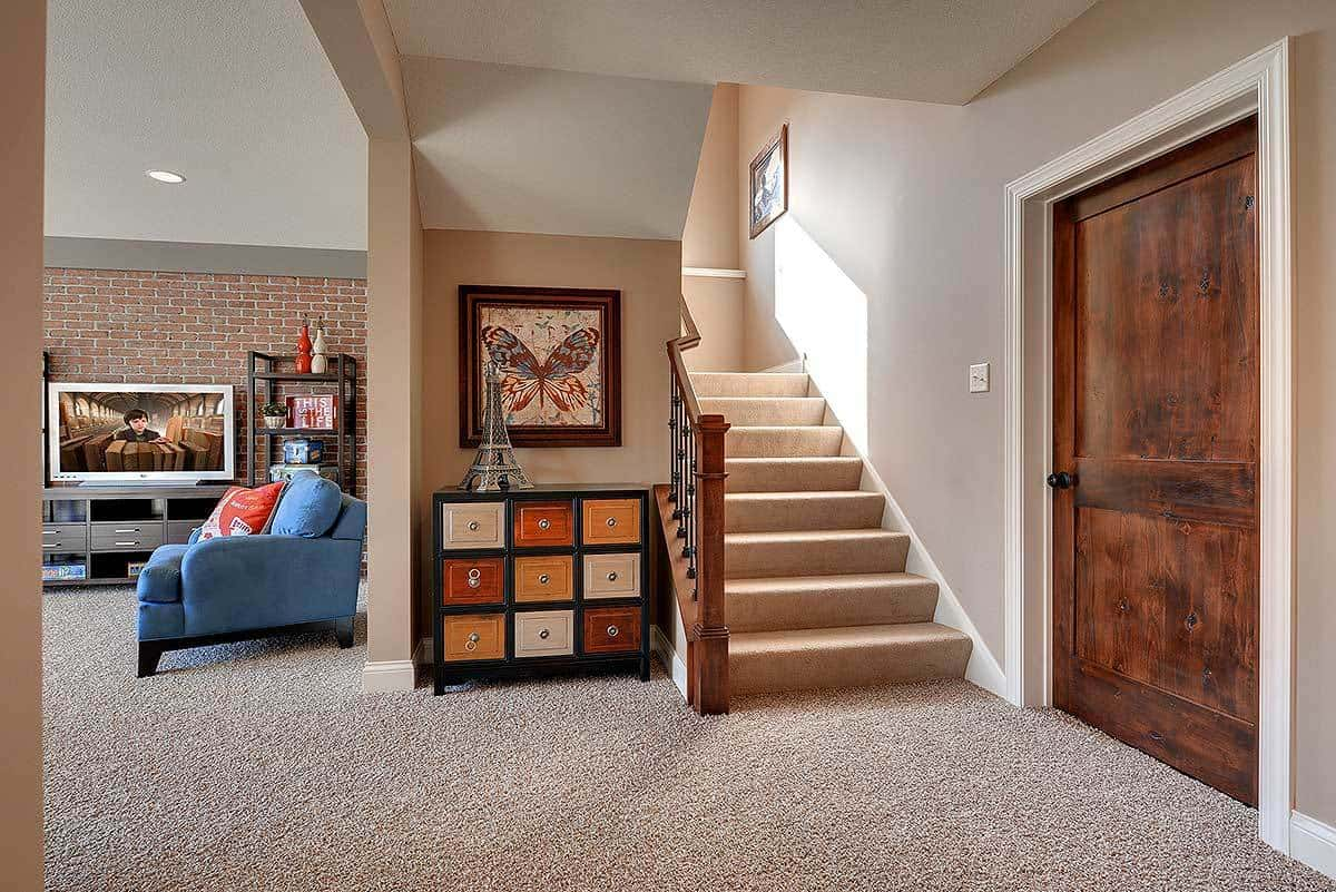 Lower level floor with a multi-colored dresser placed beside the carpeted staircase. The family room can be seen on the left side.