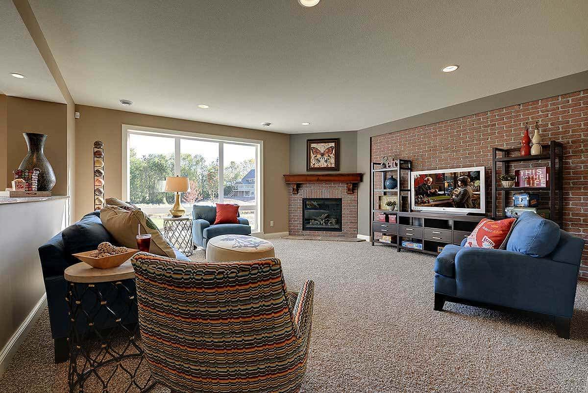 The family room is filled with various seats and a corner fireplace adorned by a butterfly artwork.