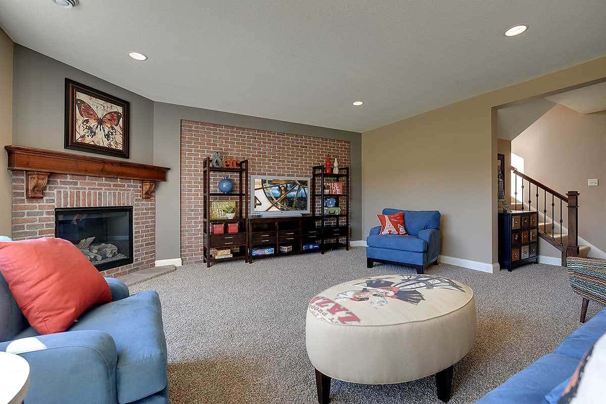 The opposite side view of the family room showing the dark wood TV cabinet against the brick accent wall.