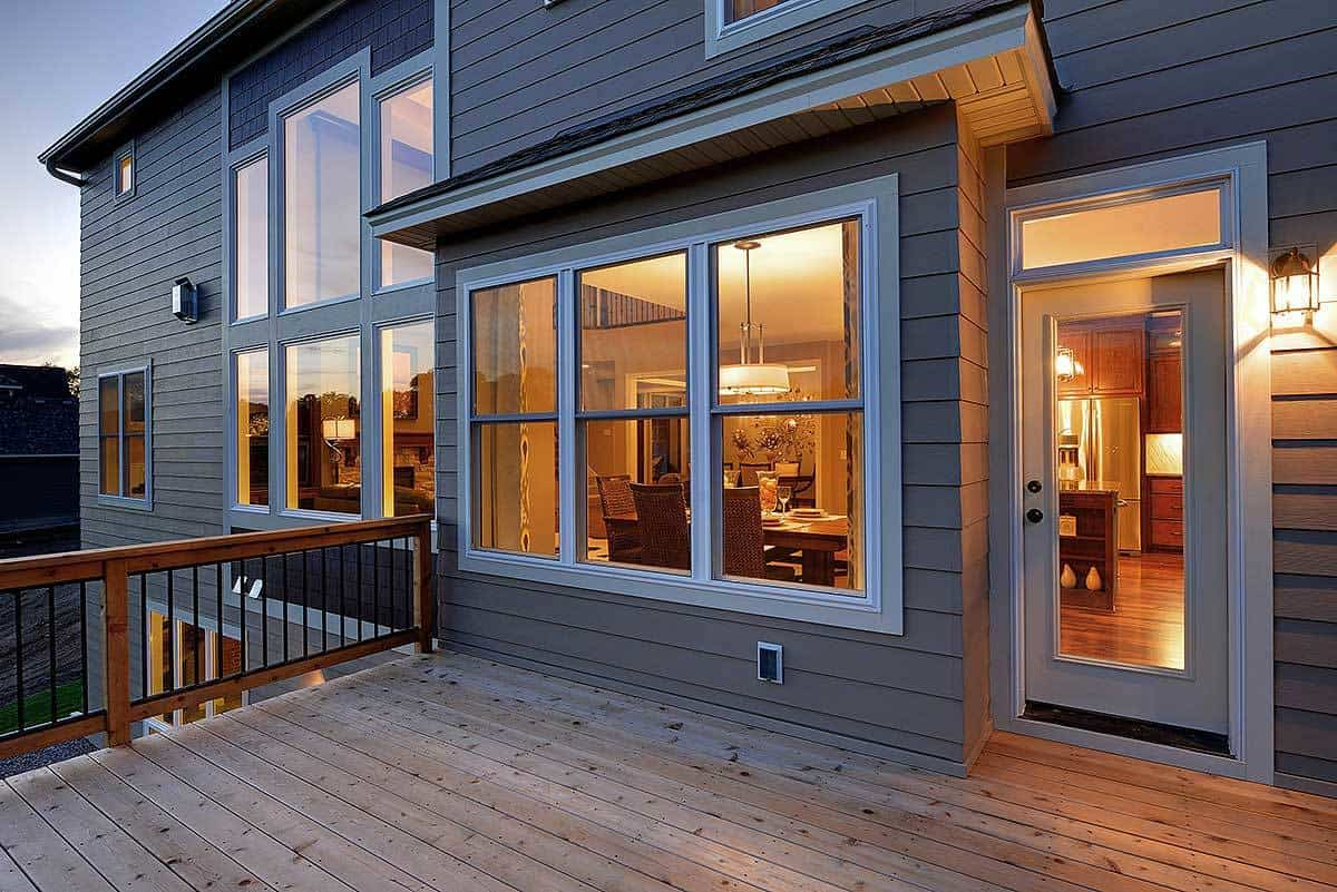 The back deck with natural hardwood flooring and wooden railings. It is situated just outside the dinette.
