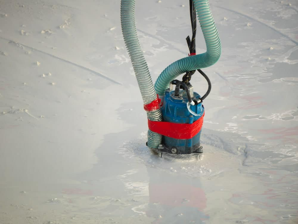A sump pump removing water from freshly applied cement.