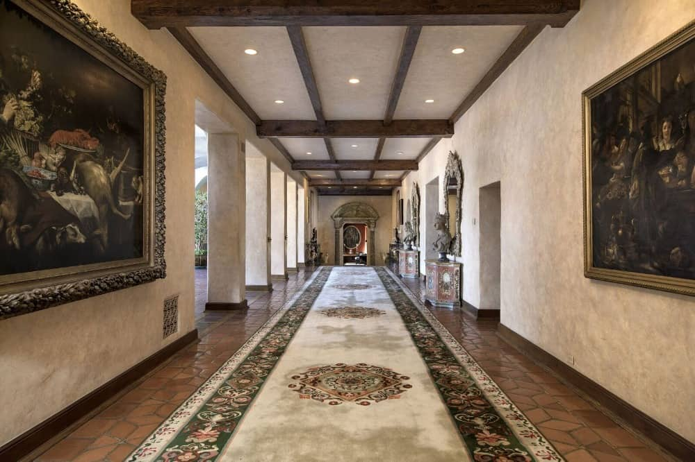 The grand hallway of the house boasts an elegant carpet walkway and large artistic wall decors. Images courtesy of Toptenrealestatedeals.com.