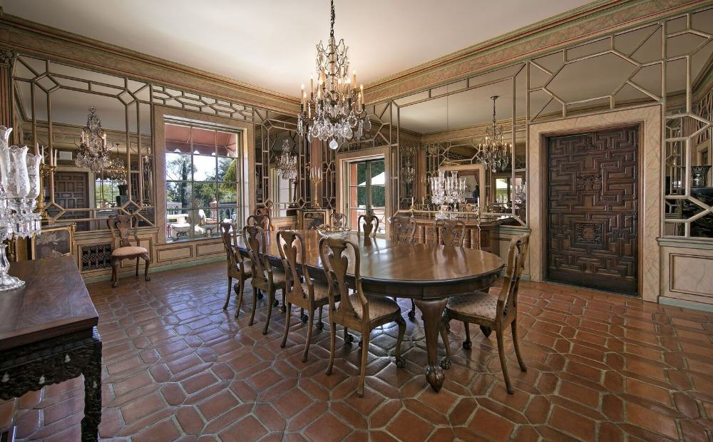 The dining room is large, and it offers a classy dining table and chairs set lighted by a glamorous chandelier. Images courtesy of Toptenrealestatedeals.com.