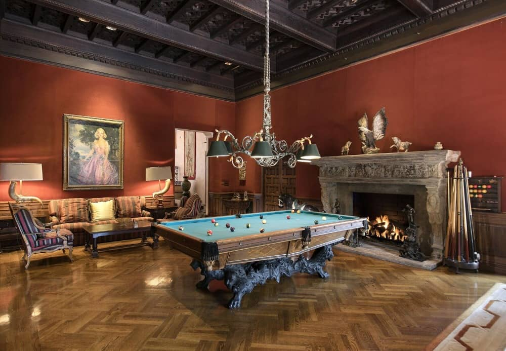 There's a game room as well, featuring this elegant billiards table with a sofa set on the side along with a large decorated stone fireplace. Images courtesy of Toptenrealestatedeals.com.
