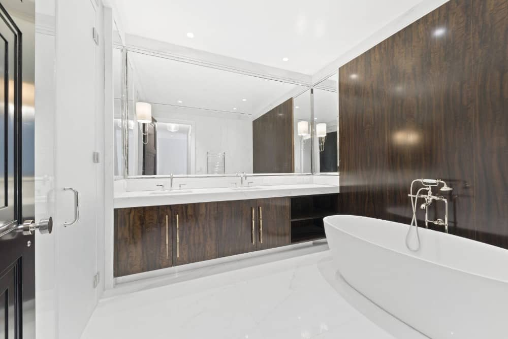 Another look at the primary bathroom showcasing the sink counter and the freestanding deep soaking tub. Images courtesy of Toptenrealestatedeals.com.