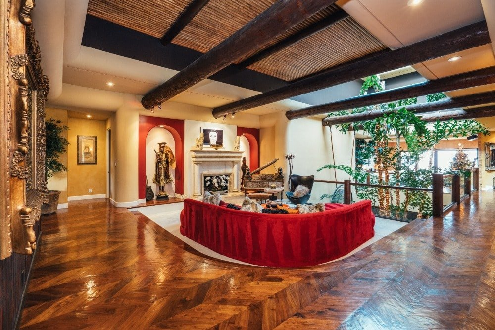This charming and spacious living room has a red curved sectional sofa matching the accents of the alcoves flanking the fireplace. These are then topped with black exposed log beams and accents from the ceiling.