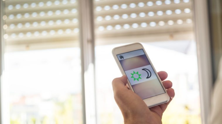 A man controlling the modern window blinds with a smart phone.