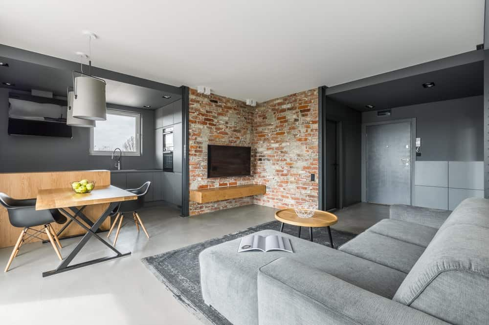 An Industrial-style room with beautiful red brick walls and metallic gray tones to pair with the L-shaped sofa.