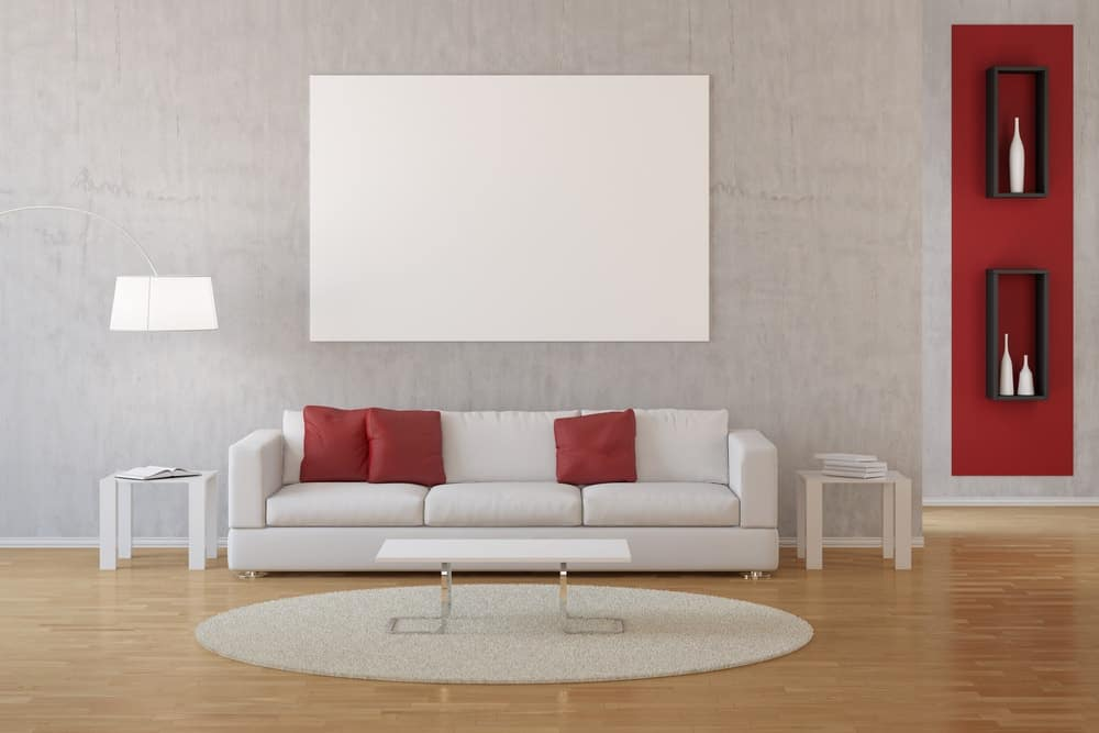 A simple living room with light tones to make the red accents of the wall and pillows stand out.