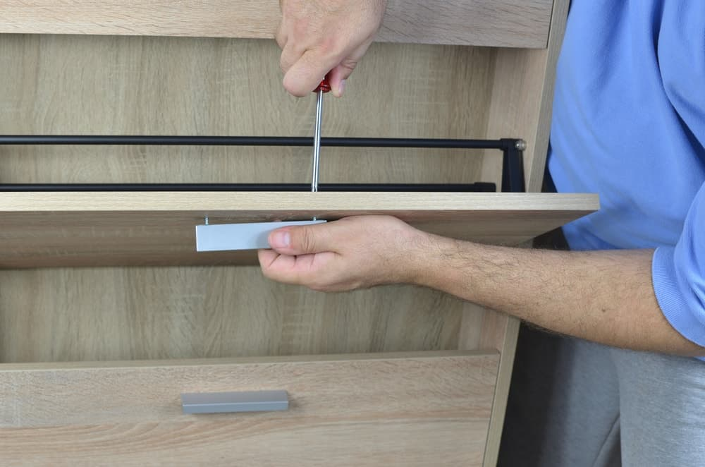 A man putting handles on a wooden shoe cabinet.