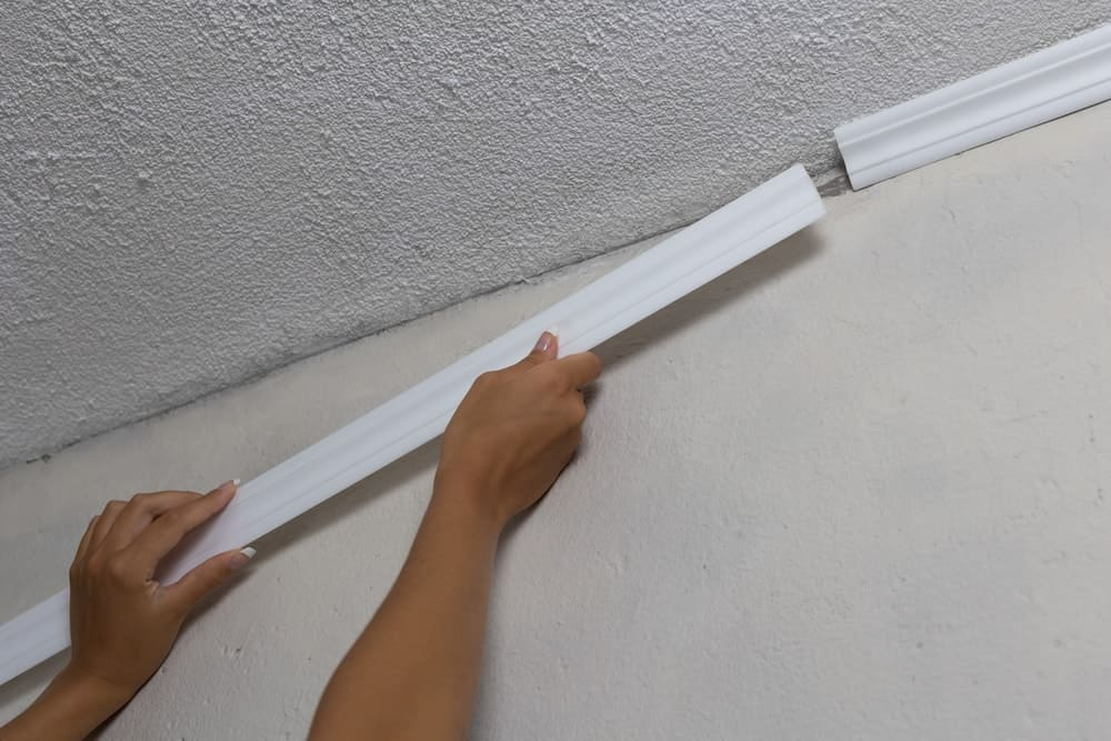 A woman installing crown molding onto the white ceiling.