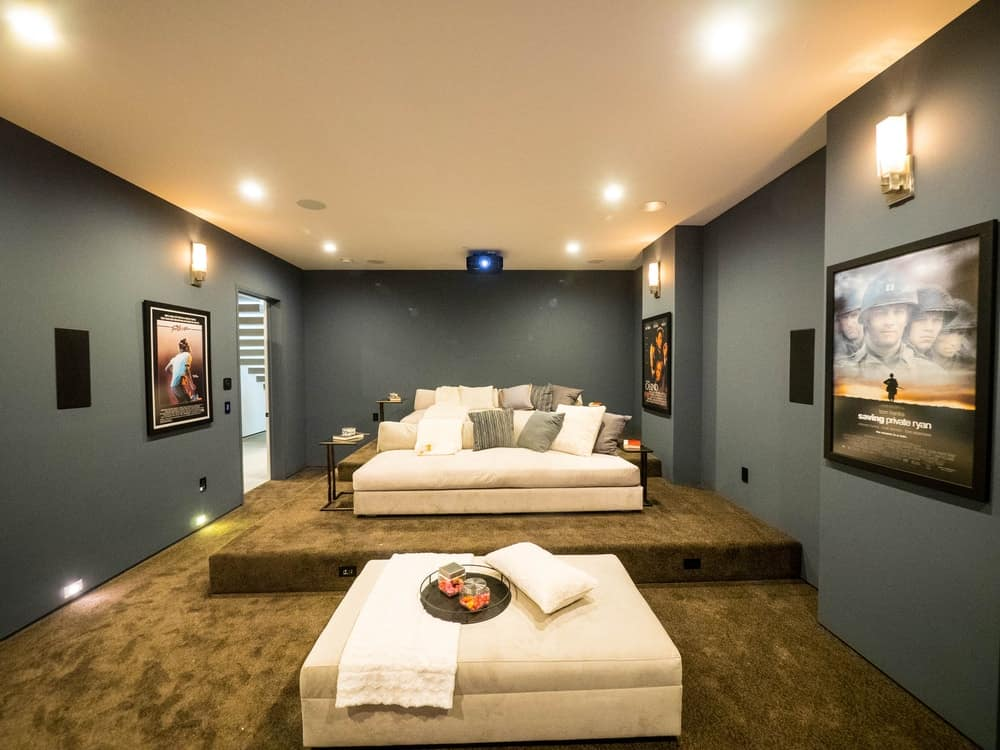 An entertainment room with raised carpeted flooring in a brown tone to emphasize the sofa set.