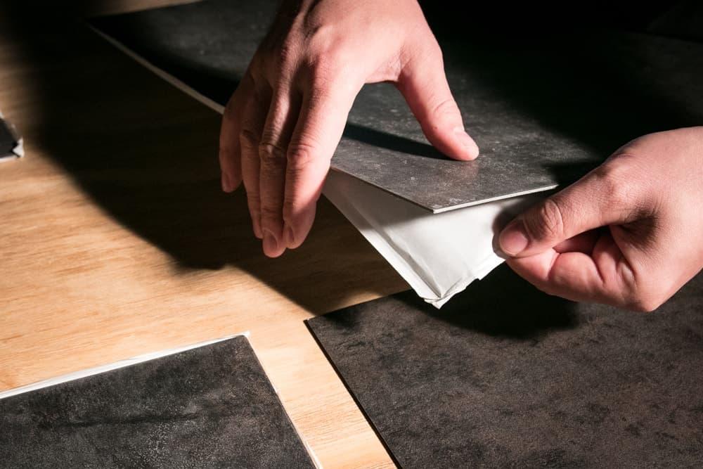 A man installing vinyl flooring tiles.