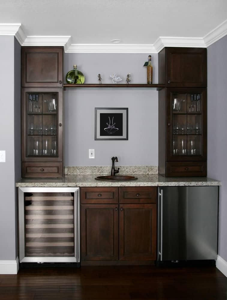 A basement that has a wet bar with dark wooden cabinets and a wine fridge.