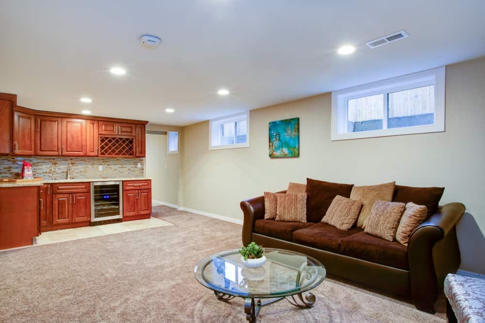 A luxurious basement with a wet bar built-in with gorgeous wooden cabinets.