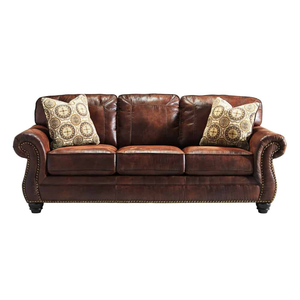 A charming sofa upholstered with brown leather complemented by the small pillows.