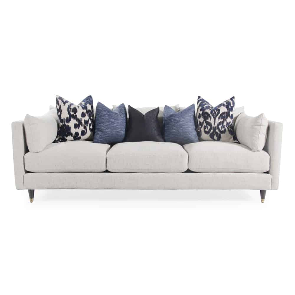 A comfortable light gray linen couch with patterned pillows on top for accent.