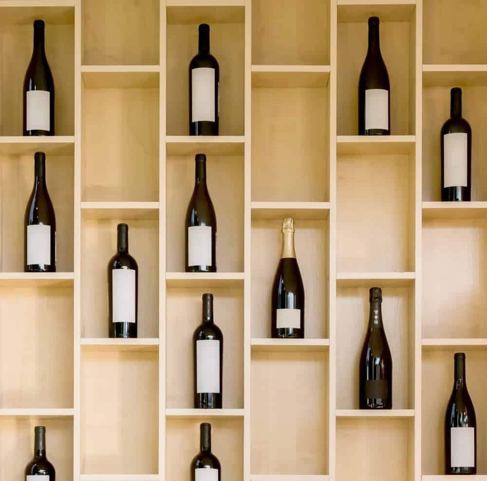 A tall built-in wooden cabinet for storing wine bottles.