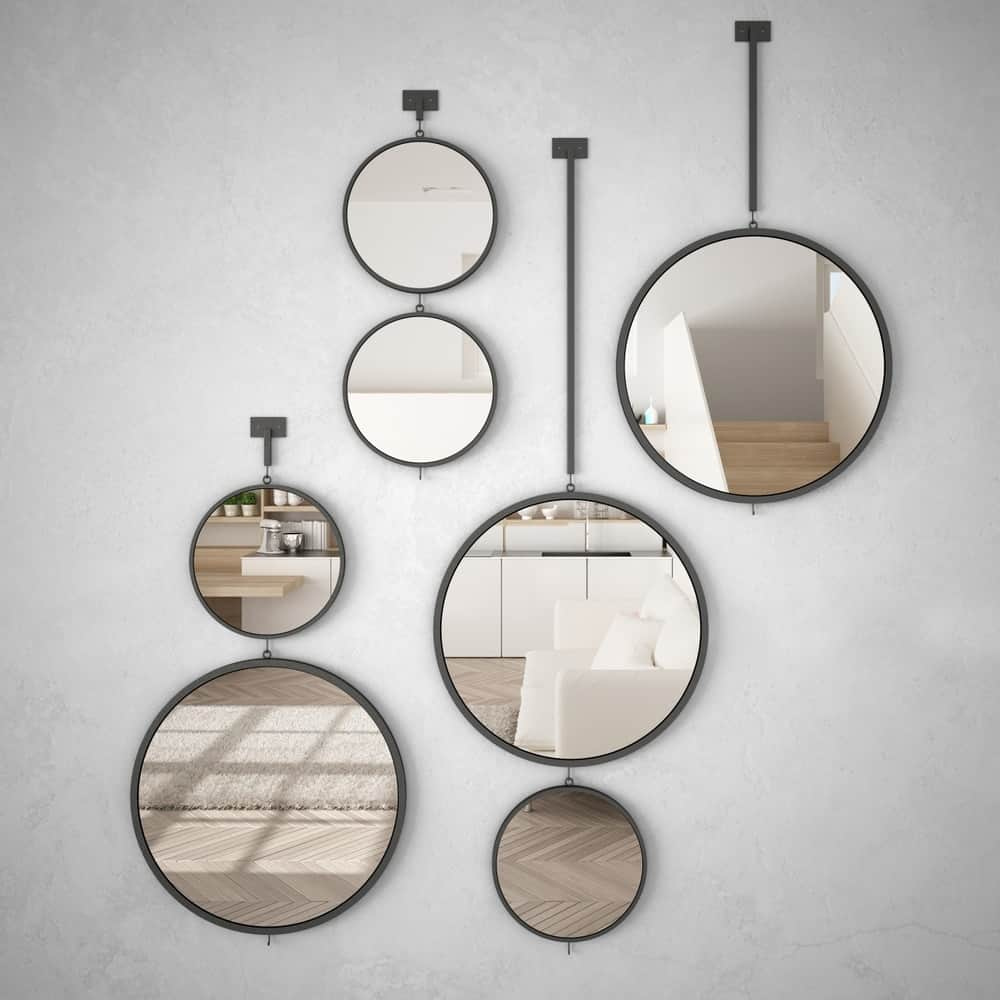 A set of artistic circular mirrors on a white wall.