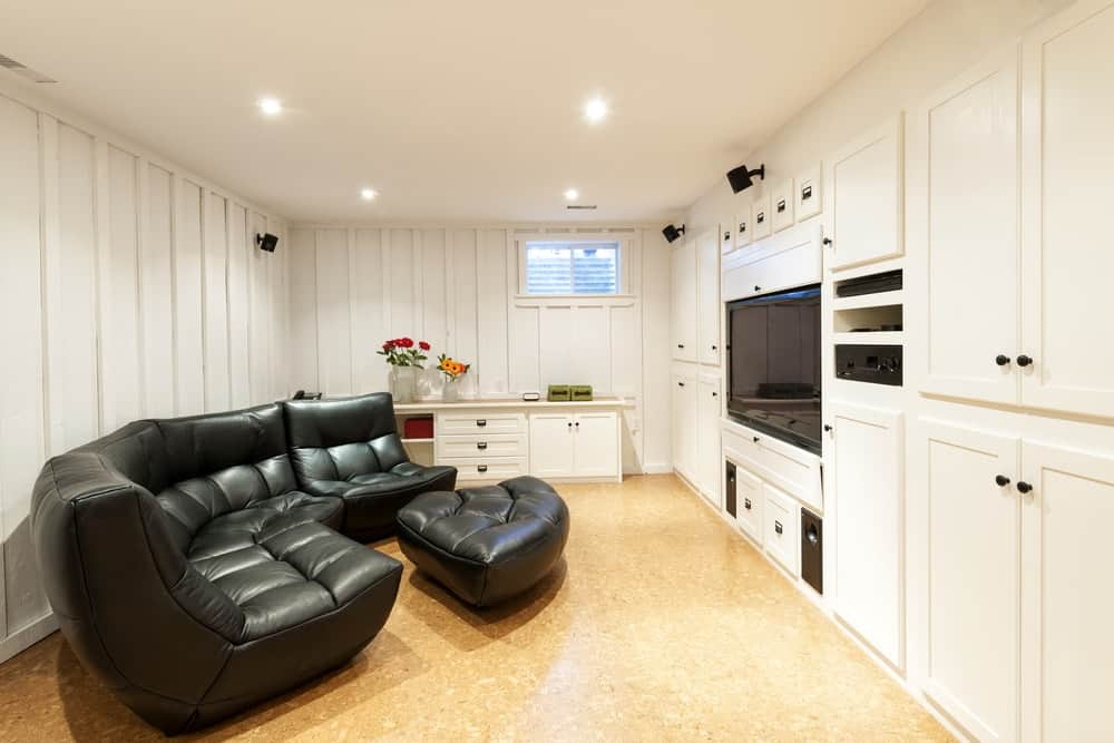 A charming basement with a large black leather curved sofa.