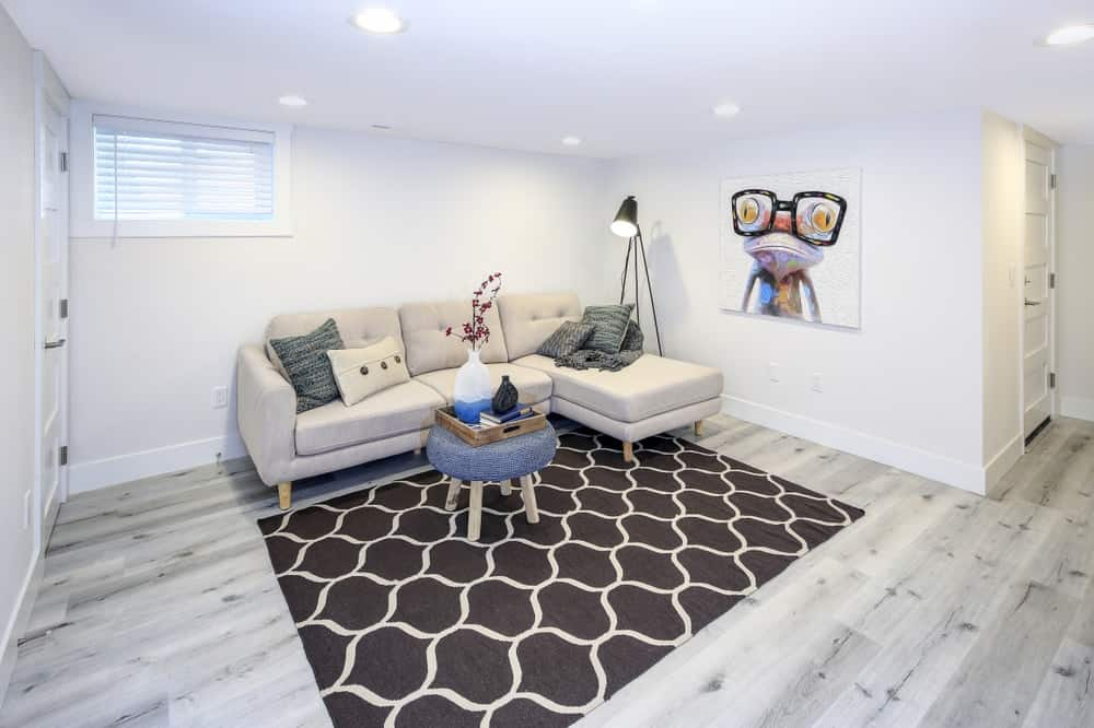 A beautiful basement with an L-shaped sofa and a dark patterned area rug.