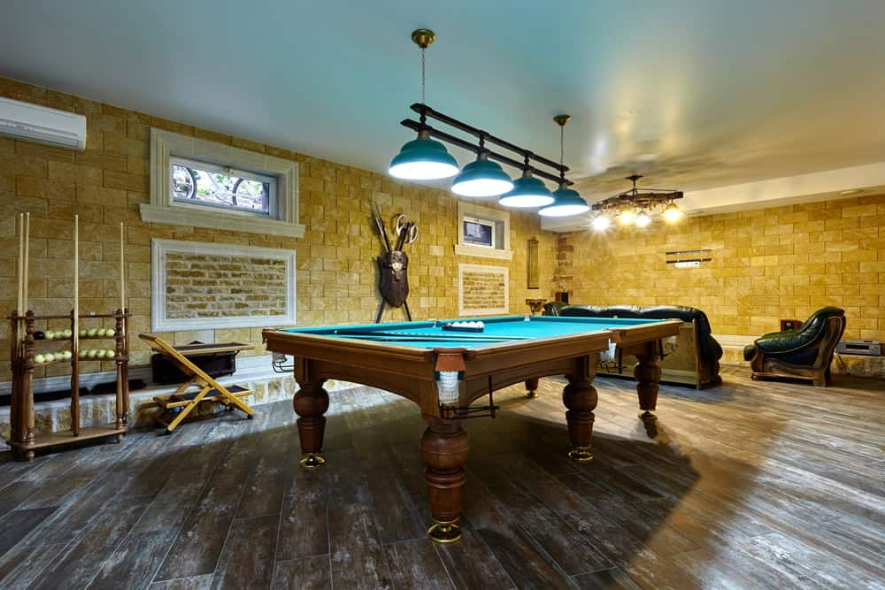 A charming basement that emphasizes its lovely billiards table.