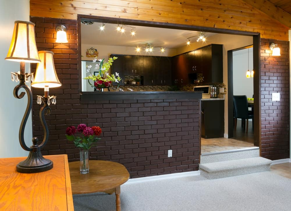 A beautiful basement that has dark brick walls complemented by the wall lamps and table lamps.