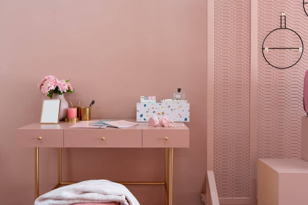 A close-up of a work area in the house that has pink walls that matches with the desk with golden accents.