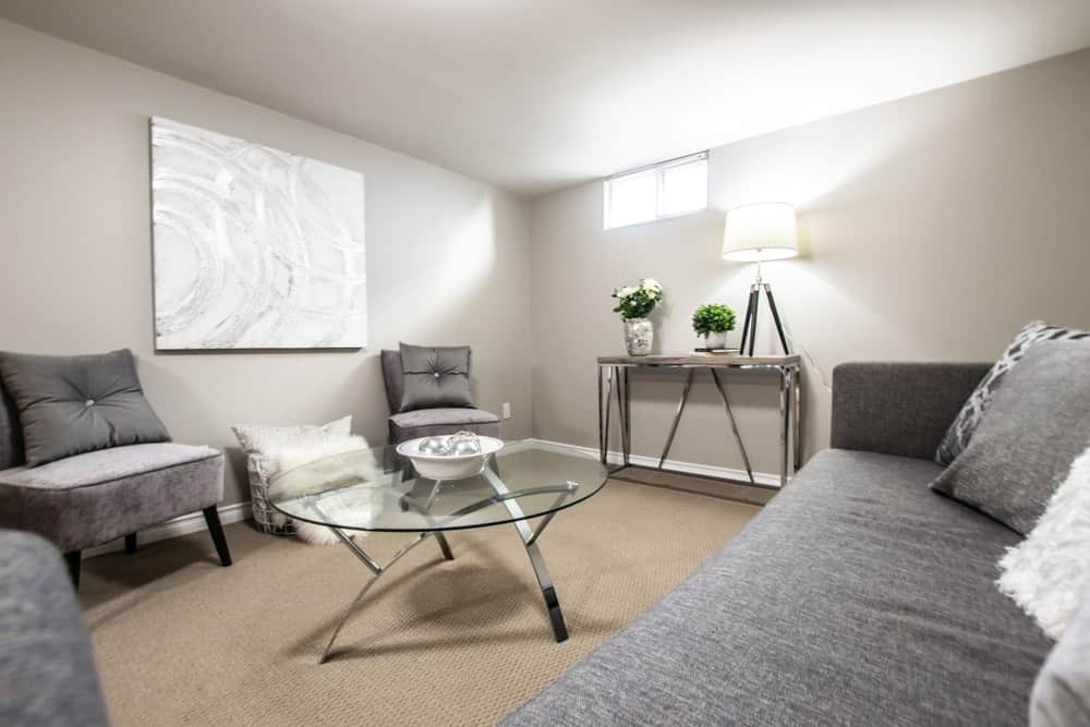 A basement with gray walls and ceiling that works well with the gray sofa set that has a darker tone.