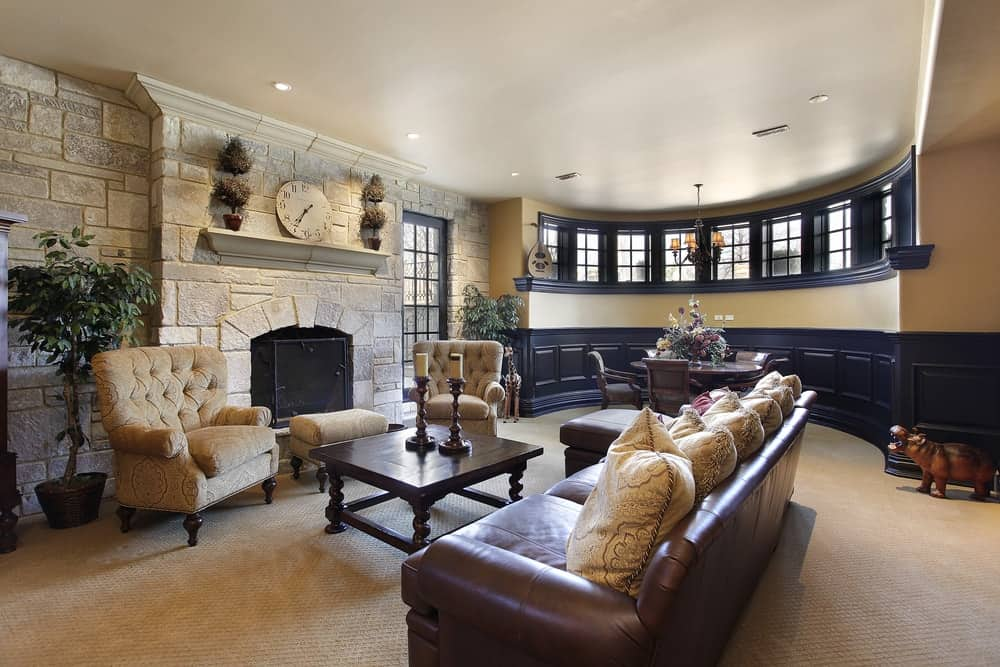 A luxurious basement that has a stone fireplace.