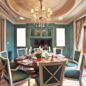 A luxurious dining room with a chandelier over the round wooden dining table.
