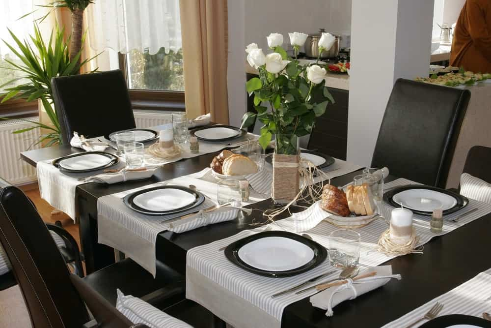 A black table setup complemented by the white floral arrangement.