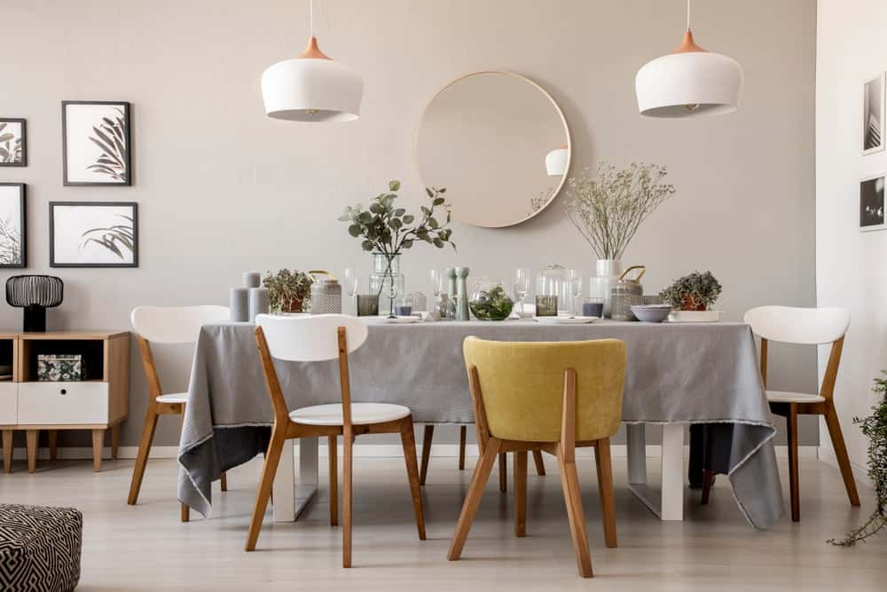 A simple bright dining room decorated with a large circular mirror.