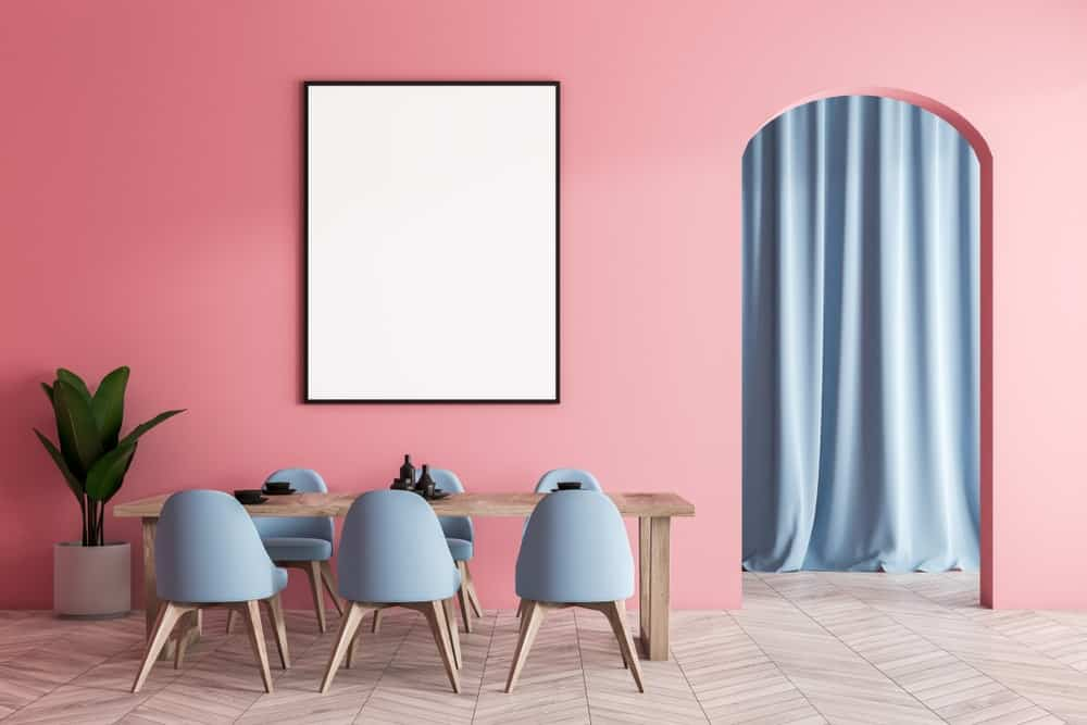 A simple and minimalist dining room with pink walls.