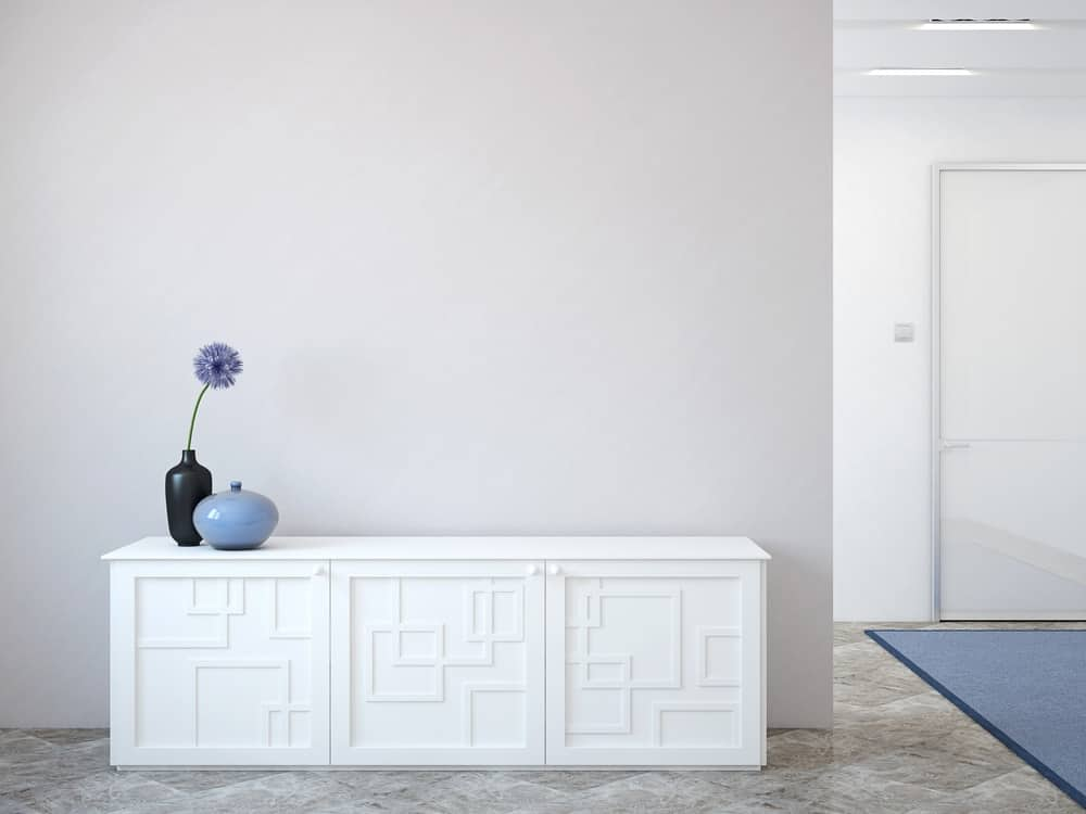 A simple foyer with a light gray wall that complements the white waist-high cabinet.