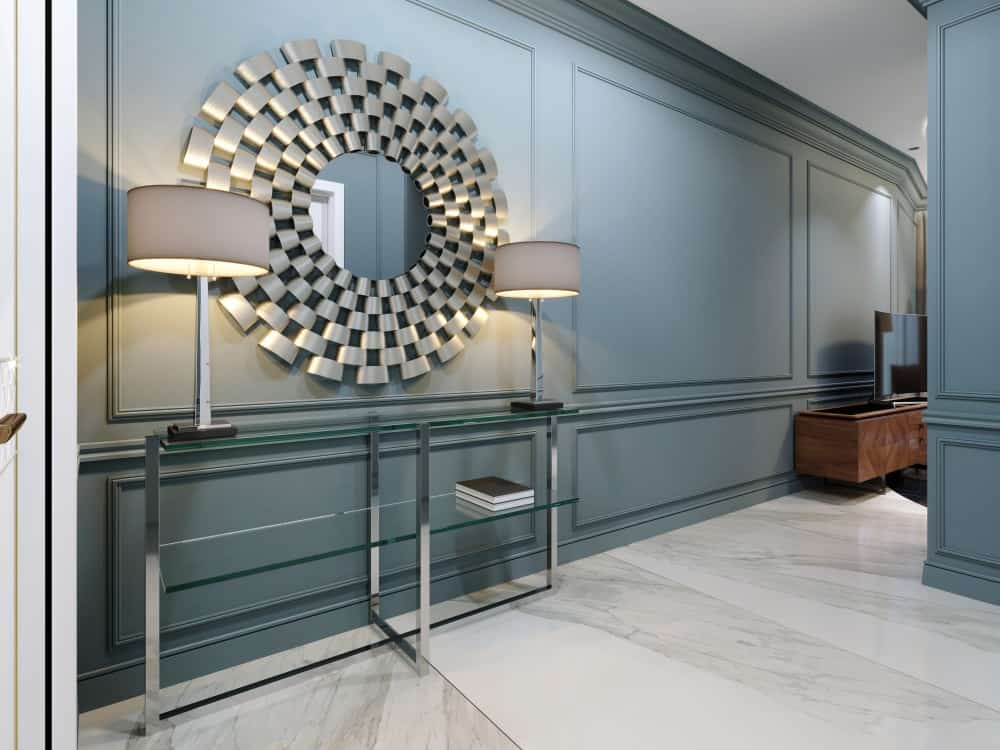 A luxurious foyer with a large decorative and artistic mirror in between two table lamps.
