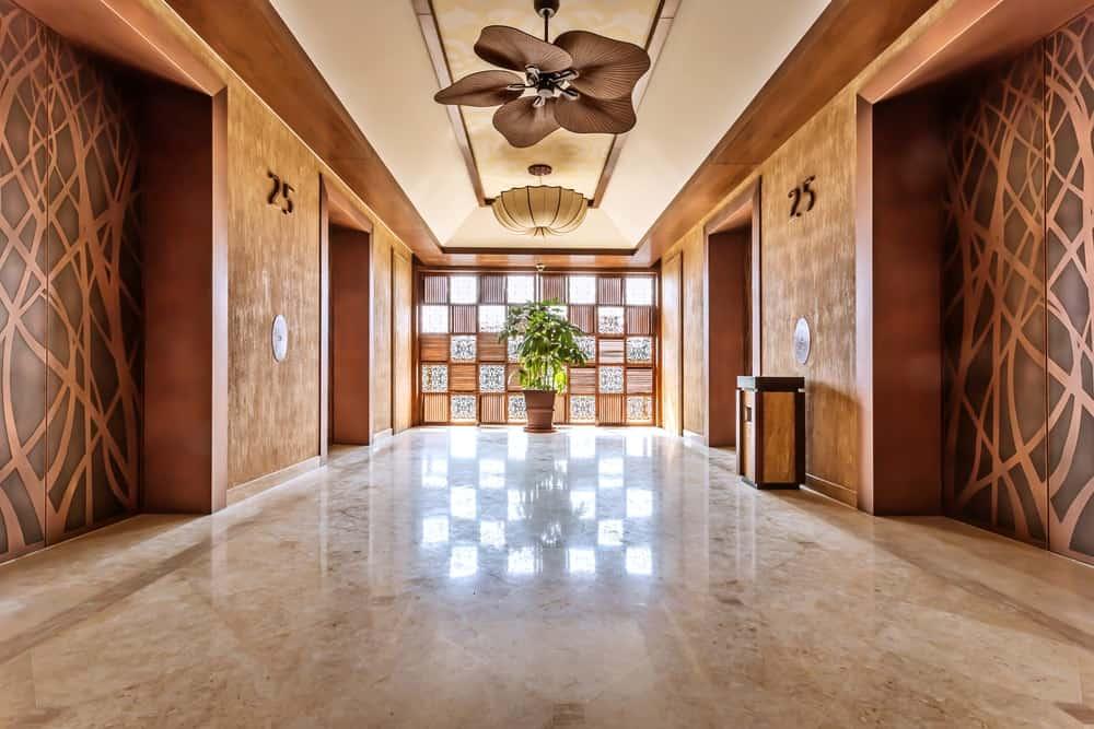 A wide luxurious foyer with a flower petal ceiling fan.