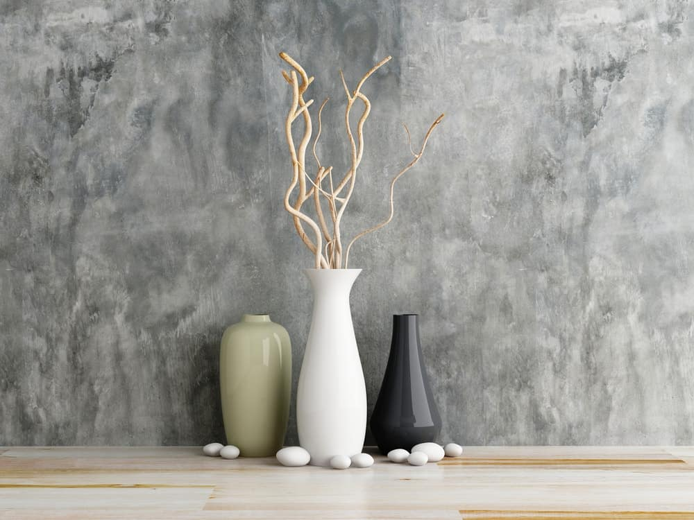 A decorative set of three vases and river stones.