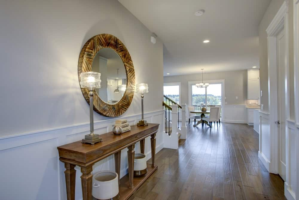 A lovely foyer with a wooden console table and a mirror above it.